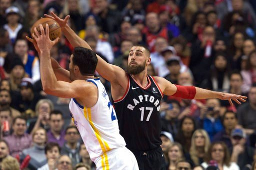 (Cole Burston/The Canadian Press via AP). Toronto Raptors center Jonas Valanciunas (17) tries to block a shot by Golden State Warriors center Zaza Pachulia (27) during the first half of an NBA basketball game Saturday, Jan. 13, 2018, in Toronto.