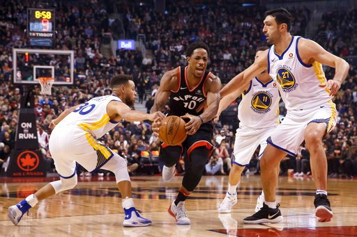(Cole Burston/The Canadian Press via AP). Toronto Raptors' DeMar DeRozan (10) tries to break through defense of Golden State Warriors center Zaza Pachulia (27) and guard Stephen Curry (30) during the first half of an NBA basketball game Saturday, Jan. ...