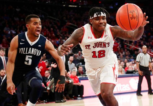 (AP Photo/Frank Franklin II). St. John's Bryan Trimble Jr. (12) chases down a loose ball as Villanova's Phil Booth (5) watches during the first half of an NCAA college basketball game Saturday, Jan. 13, 2018, in New York.