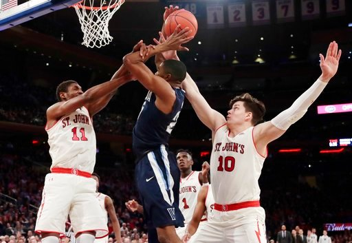 (AP Photo/Frank Franklin II). St. John's Tariq Owens (11) and Amar Alibegovic (10) defend Villanova's Mikal Bridges during the first half of an NCAA college basketball game Saturday, Jan. 13, 2018, in New York.