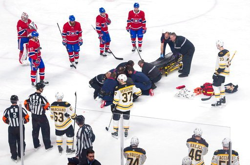 (Graham Hughes/The Canadian Press via AP). Players from the Montreal Canadiens and Boston Bruins look on as Canadiens' Phillip Danault tended to by paramedics after he was hit in the head by a puck on a shot by Bruins' Zdeno Chara (33) during second pe...