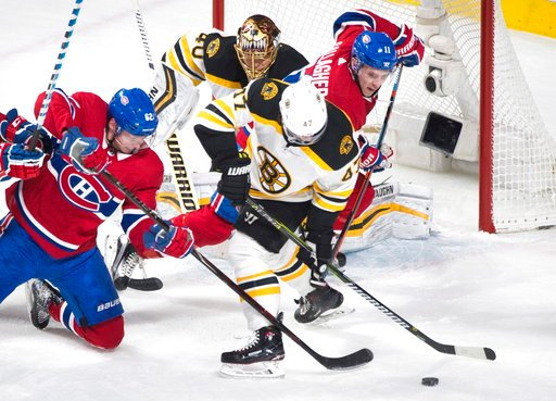 (Graham Hughes/The Canadian Press via AP). Boston Bruins goaltender Tuukka Rask looks on as Montreal Canadiens' Artturi Lehkonen (62) and Brendan Gallagher (11) and Bruins' Torey Krug battle for the puck during second period NHL hockey action in Montre...