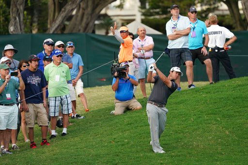 (AP Photo/Marco Garcia). Brian Harman, center right, hits his ball back onto the 16th fairway during the third round of the Sony Open golf tournament, Saturday Jan. 13, 2018, in Honolulu.