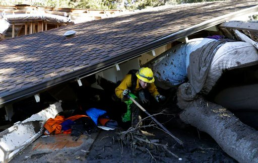 (AP Photo/Marcio Jose Sanchez). Colette Layton, bottom, of the Atascadero Fire Dept, searches a home Saturday, Jan. 13, 2018, in Montecito, Calif.  Most of the people of Montecito, a town usually known for its serenity and luxury, were under orders to ...