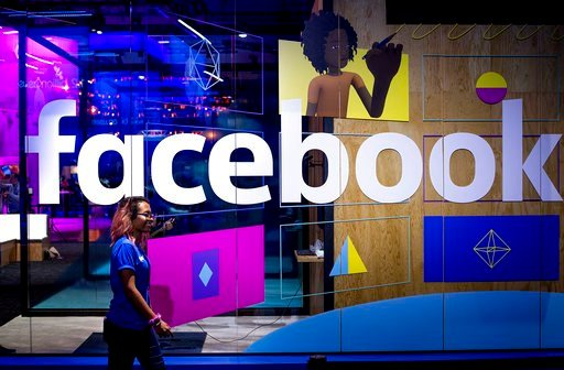 (AP Photo/Noah Berger, File). FILE - In this Tuesday, April 18, 2017, file photo, a conference worker passes a demo booth at Facebook's annual F8 developer conference, in San Jose, Calif. Facebook Inc. reports earnings Wednesday, Jan. 31, 2018.