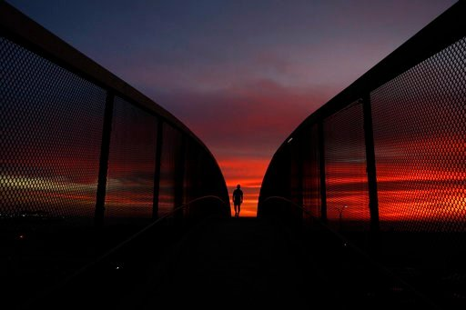 (AP Photo/Jae C. Hong, File). FILE - In this Jan. 16, 2018 file photo, Mark Waissar, 49, is silhouetted against sunset as he walks on an overpass above the Pacific Coast Highway in Santa Monica, Calif. California's water managers are carrying out their...