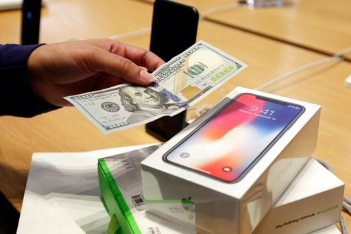 (AP Photo/Richard Drew, File). FILE - In this Friday, Nov. 3, 2017, file photo, a customer hands over cash as she pays for an iPhone X at the Apple Store on New York's Fifth Avenue. Apple is facing some thorny questions about its best-selling product, ...