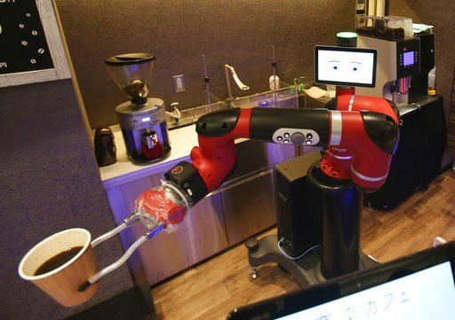 """(AP Photo/Koji Sasahara). Robot barista named """"Sawyer"""" makes a coffee at Henn-na Cafe, Japanese meaning """"Strange Cafe""""in Tokyo, Friday, Feb. 2, 2018. The cafe's robot barista brews and serves coffee as the rapidly aging country seeks to adapt to shrink..."""