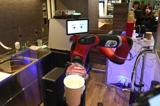 """(AP Photo/Koji Sasahara). Robot barista named """"Sawyer"""" makes a coffee at Henn-na Cafe, meaning """"Strange Cafe"""" in Japanese, in Tokyo, Friday, Feb. 2, 2018. The cafe's robot barista brews and serves coffee as the rapidly aging country seeks to adapt to s..."""