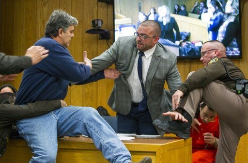 (Cory Morse/The Grand Rapids Press via AP). Randall Margraves, father of three victims of Larry Nassar , left, lunges at Nassar, bottom right, Friday, Feb. 2, 2018, in Eaton County Circuit Court in Charlotte, Mich.  The incident came during the third a...