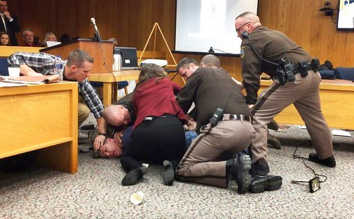 (Kim Kozlowski/Detroit News via AP). Eaton County Sheriff's deputies restrain Randall Margraves, father of three victims of Larry Nassar, Friday, Feb. 2, 2018, in Eaton County Circuit Court in Charlotte, Mich.  The incident came during the third and fi...