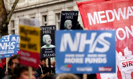 (Yui Mok/PA via AP). People wave banners depicting Britain's Prime Minister Theresa May, during a protest march in support of the National Health Service (NHS), as winter conditions are thought to have put severe strain on health services, in London Sa...