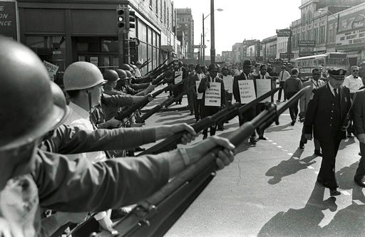 (AP Photo/Charlie Kelly, File). FILE-In this March 29, 1968 file photo, striking Memphis sanitation workers march past Tennessee National Guard troops with fixed bayonets during a 20-block march to City Hall in Memphis, Tenn. Fifty years ago, two sanit...