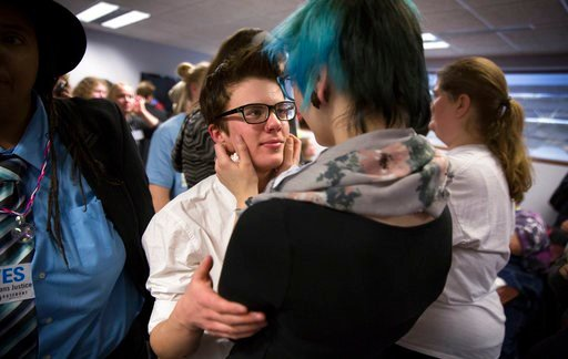 (Leila Navidi/Star Tribune via AP). FILE - In this Dec. 4, 2014 file photo, Elliott Kunerth, 17, a transgender male high school student in Mankato, hugs his girlfriend, Kelsi Pettit, 17, after the Minnesota State High School League board voted to pass ...