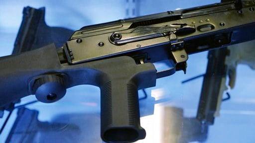 "(AP Photo/Rick Bowmer, File). FILE - In this Oct. 4, 2017, file photo, a device called a ""bump stock"" is attached to a semi-automatic rifle at the Gun Vault store and shooting range in South Jordan, Utah. Some states and cities are taking the lead on b..."