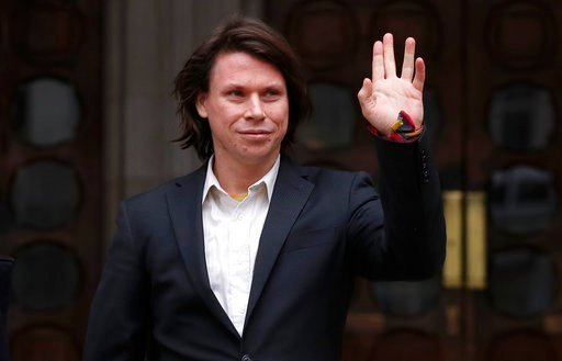 (AP Photo/Kirsty Wigglesworth). Lauri Love waves to supporters outside The Royal Courts of Justice in London, Monday, Feb. 5, 2018. The ruling in Lauri Love's appeal against extradition to the United States, where he faces solitary confinement and a po...
