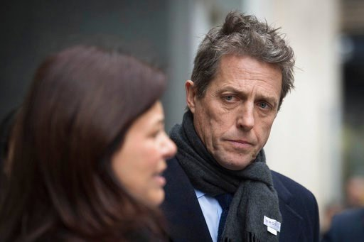 ( Stefan Rousseau/PA via AP). British actor Hugh Grant leaves the Rolls Building in London after they settled their phone hacking claims against Mirror Group Newspapers  Monday Feb. 5, 2018.   Grant was at the High Court when the details of the settlem...
