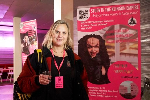 """(AP Photo/David Keyton). In this photo taken in Stockholm on Saturday, Feb. 3 2018, Star Trek fan Eva Friberg poses for a photo next to a poster seeking to attract students to courses at the military academy on the Klingon home world (""""find your inner ..."""