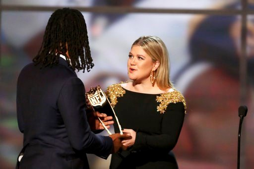 (Michael Zorn/NFL via AP). In this photo provided by the NFL, Todd Gurley of the Los Angeles Rams, left, accepts the award from Kelly Clarkson for The Associated Press 2017 NFL Offensive Player of the Year at the 7th Annual NFL Honors at the Cyrus Nort...