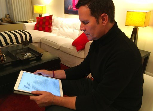 (AP Photo/Yvonne Lee). Juan Carlos Cruz reads from his tablet during an interview with The Associated Press in Philadelphia, Sunday Feb. 4, 2017. Cruz says Pope Francis received a letter he wrote in 2015 detailing the sexual abuse he suffered at the ha...