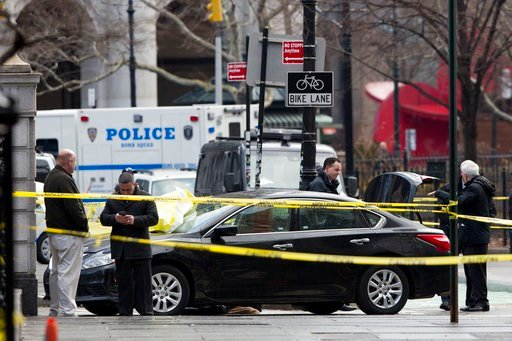 (AP Photo/Mark Lennihan). Police investigate a car stopped in front of a security gate, Monday, Feb. 5, 2018, at City Hall in New York. Police say a man is dead after he drove the car up to the gate and shot himself in the head.