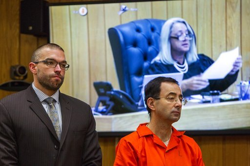 (Cory Morse /The Grand Rapids Press via AP). Larry Nassar, right, listens near defense attorney Matthew Newberg as Judge Janice Cunningham (pictured on the monitor) sentences Nassar at Eaton County Circuit Court in Charlotte, Mich.,  Monday, Feb. 5, 20...