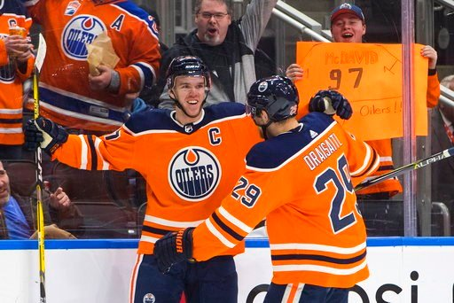 (Jason Franson/The Canadian Press via AP). Edmonton Oilers' Connor McDavid (97) and Leon Draisaitl (29) celebrate a goal against the Tampa Bay Lightning during second period NHL hockey action in Edmonton, Alberta, Monday, Feb. 5, 2018.