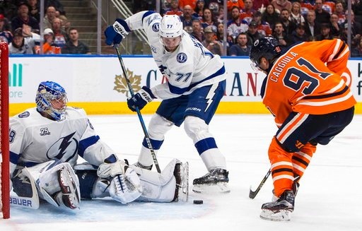 (Jason Franson/The Canadian Press via AP). Tampa Bay Lightning' goalie Andrei Vasilevskiy (88) makes the save as Victor Hedman (77) and Edmonton Oilers' Drake Caggiula (91) go for the rebound during second period NHL hockey action in Edmonton, Alberta,...