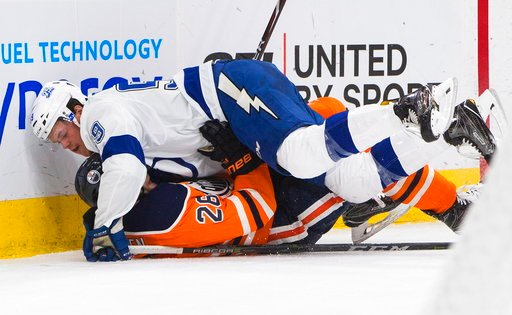 (Jason Franson/The Canadian Press via AP). Tampa Bay Lightning' Slater Koekkoek (29) lands on top of Edmonton Oilers' Iiro Pakarinen (26) during second period NHL hockey action in Edmonton, Alberta, Monday, Feb. 5, 2018.