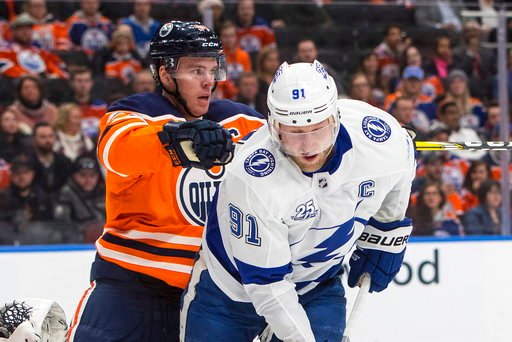 (Jason Franson/The Canadian Press via AP). Tampa Bay Lightning' Steven Stamkos (91) is cross checked by Edmonton Oilers' Connor McDavid (97) during first period NHL action in Edmonton, Alberta, Monday, Feb. 5, 2018.