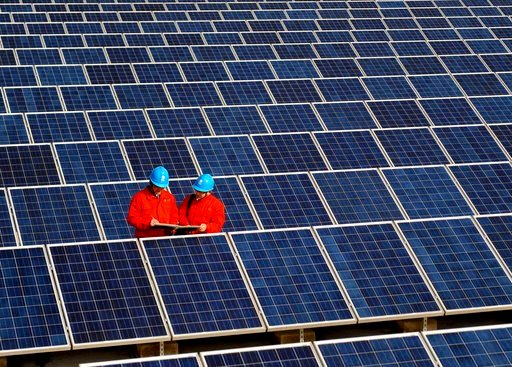 (Chinatopix via AP, File). FILE - In this Feb. 7, 2012, file photo, workers check solar panels at a solar power station on a factory roof in Changxing in eastern China's Zhejiang province. One of China's biggest makers of solar panels said Tuesday, Feb...