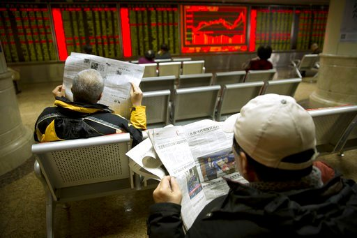 (AP Photo/Mark Schiefelbein). Investors read newspapers as they monitor stock prices at a brokerage house in Beijing, Tuesday, Feb. 6, 2018. Shares tumbled in Asia on Tuesday after a wild day for U.S. markets that resulted in the biggest drop in the Do...
