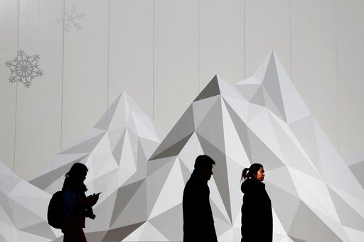 (AP Photo/Jae C. Hong). People walk past an advertisement at the Olympic Park ahead of the 2018 Winter Olympics in Gangneung, South Korea, Tuesday, Feb. 6, 2018. The Gangneung coastal cluster is hosting the ice sports, including figure skating, speed s...
