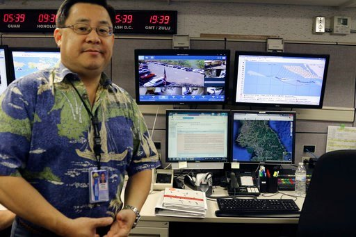 (AP Photo/Jennifer Sinco Kelleher, File). FILE - In this July 21, 2017 file photo, Jeffrey Wong, the Hawaii Emergency Management Agency's operations officer, shows computer screens monitoring hazards at the agency's headquarters in Honolulu. The photo ...