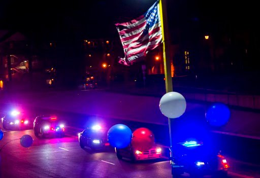 (Dougal Brownlie/The Gazette via AP). An American flag waves in the wind as a police procession travels along South Nevada Avenue for El Paso County Sheriff's Deputy Micah Flick, Monday, Feb. 5, 2018, in Colorado Springs, Colo. Flick was shot and kille...