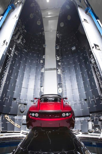 (SpaceX via AP). This Dec. 6, 2017 photo made available by SpaceX shows a Tesla car next to the fairing of a Falcon Heavy rocket in Cape Canaveral, Fla. For the Heavy's inaugural flight, the rocket will carry up Elon Musk's roadster. In addition to Spa...