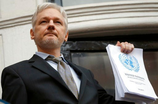 (AP Photo/Frank Augstein, File). FILE - This is a Friday, Feb. 5, 2016 file photo of WikiLeaks founder Julian Assange holds a U.N. report as he speaks on the balcony of the Ecuadorian Embassy in London. A British judge is scheduled to rule on Tuesday F...