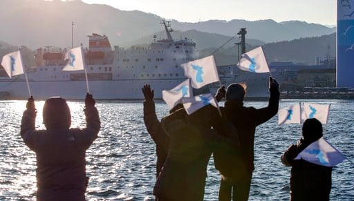 (Kim Do-hoon/Yonhap via AP). South Koreans wave unification flags as North Korea's Mangyongbong-92 ferry carrying North Korea's members of art troupe approaching to Mukho Port in Donghae, South Korea, Tuesday, Feb. 6, 2018. The art troupe, led by Hyon ...