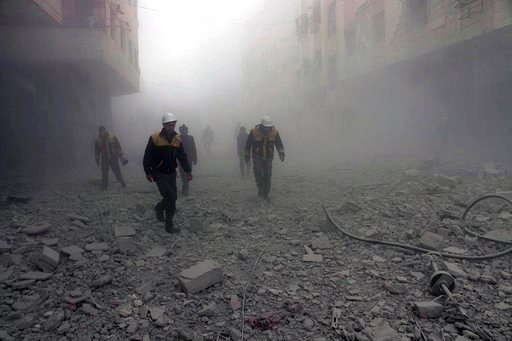 (Syrian Civil Defense White Helmets via AP). This photo provided by the Syrian Civil Defense group known as the White Helmets, shows civil defense workers searching for survivors after airstrikes hit a rebel-held suburb near Damascus, Syria, Monday, Fe...