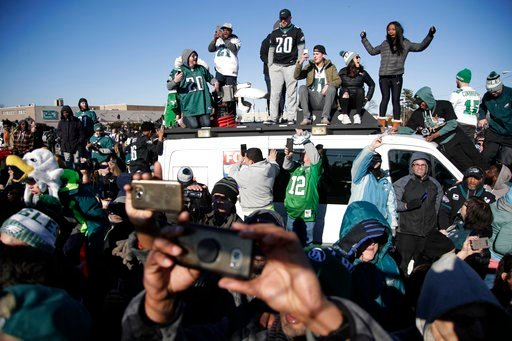 (AP Photo/Julio Cortez). Philadelphia Eagles stand atop a news van while waiting for the team to deplane Monday, Feb. 5, 2018, at Philadelphia International Airport a day after defeating the New England Patriots in Super Bowl 52.