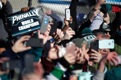 (AP Photo/Julio Cortez). Philadelphia Eagles fan hold up smartphones as the team's airplane arrives at Philadelphia International Airport a day after defeating the New England Patriots in Super Bowl 52 in Minneapolis, Monday, Feb. 5, 2018.