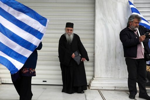 (AP Photo/Yorgos Karahalis). A Greek Orthodox priest stands between protesters holding Greek flags during a rally in Athens, Sunday, Feb. 4, 2018. Protesters were arriving in the Greek capital for what is expected to be a massive rally Sunday afternoon...