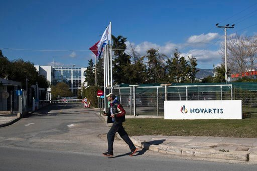 (AP Photo/Petros Giannakouris). A man crosses the street outside the Novartis Greek offices in Athens, on Tuesday, Feb. 6, 2018. Greece's government says it has evidence that senior politicians from the previous administration were involved in a briber...