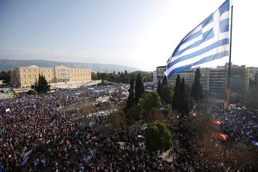 (AP Photo/Thanassis Stavrakis). A giant Greek flag hangs from a crane waves over protesters during a rally in Athens, Sunday, Feb. 4, 2018. Protesters from across Greece were thronging the Greek capital's main square outside parliament Sunday to protes...