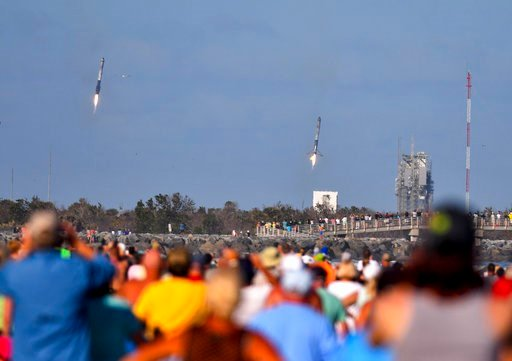 (Malcolm Denemark/Florida Today via AP). Crowds on the beach in Cape Canaveral watch two of the three boosters from the SpaceX Falcon Heavy launched Tuesday, Feb. 6, 2018, from Kennedy Space Center's Pad 39A land moments apart at Landing Zones 1 and 2 ...