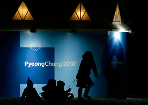 (AP Photo/Aaron Favila). Children are pulled on a bobsleigh, in front of the 2018 Winter Olympics sign, in Pyeongchang, South Korea, Tuesday, Feb. 6, 2018.