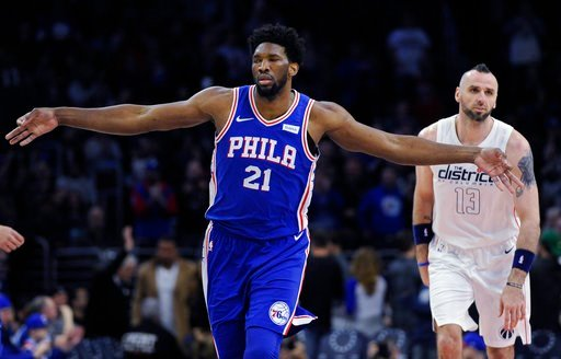 (AP Photo/Michael Perez). Philadelphia 76ers' Joel Embiid (21) celebrates after scoring three points while Washington Wizards' Marcin Gortat looks on in the first half of an NBA basketball game, Tuesday, Feb 6, 2018, in Philadelphia.