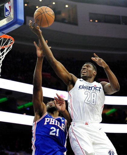 (AP Photo/Michael Perez). Washington Wizards' Ian Mahinmi (28) drives the ball to the basket over Philadelphia 76ers' Joel Embiid (21) in the first half of an NBA basketball game, Tuesday, Feb 6, 2018, in Philadelphia.
