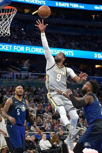 (AP Photo/Phelan M. Ebenhack). Cleveland Cavaliers guard Dwyane Wade (9) puts up a shot between Orlando Magic forward Marreese Speights (5) and guard Shelvin Mack (7) during the first half of NBA basketball game Tuesday, Feb. 6, 2018, in Orlando, Fla.
