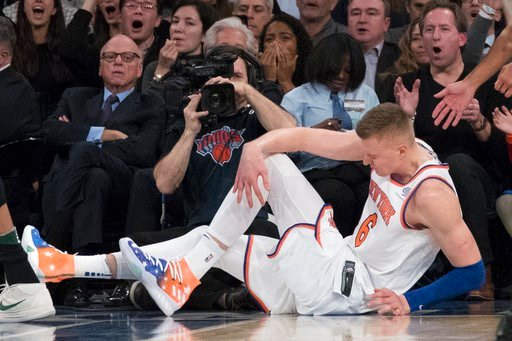 (AP Photo/Mary Altaffer). New York Knicks forward Kristaps Porzingis clutches his knee after a fall during the first half of the team's NBA basketball game against the Milwaukee Bucks, Tuesday, Feb. 6, 2018, at Madison Square Garden in New York.